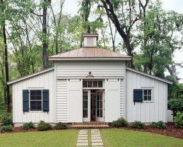 Based on the design of an 1860s smokehouse, this Spring Island, South Carolina guesthouse is embellished with a standing-seam copper roof and barn doors that slide open to reveal French doors leading to the great room within.  Photography: Richard Leo Johnson/Atlantic Archives
