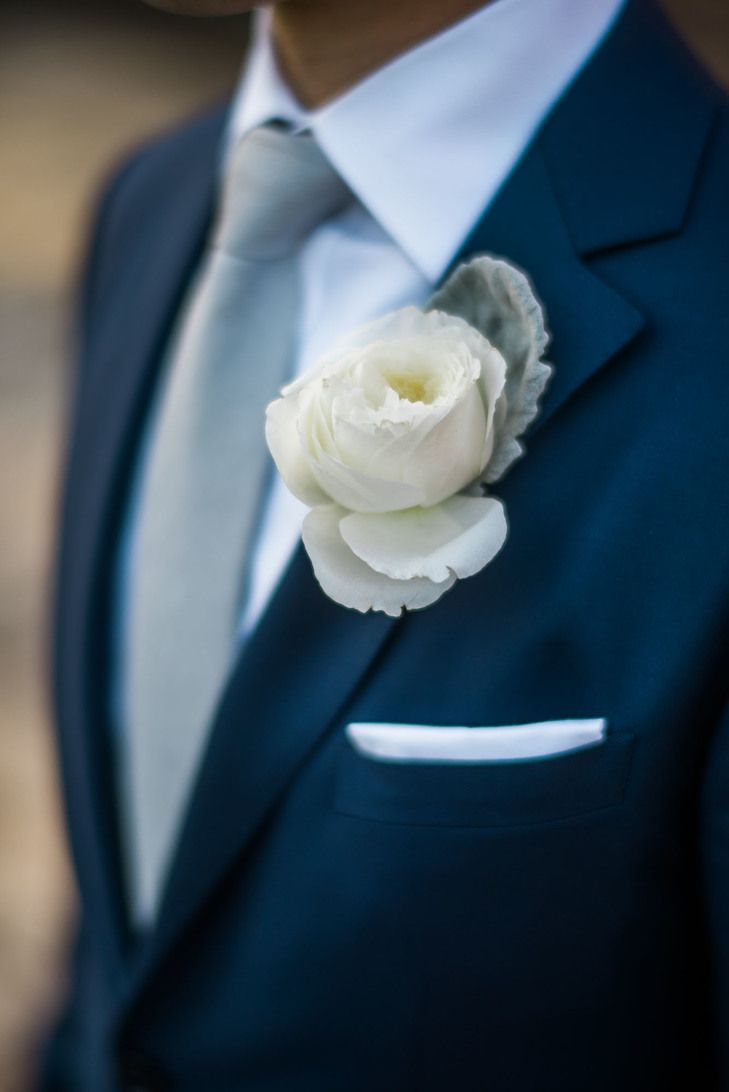 Ivory rose and dusty miller boutonniere pinned to the lapel of a midnight blue suit jacket by Enzo Custom Clothiers
