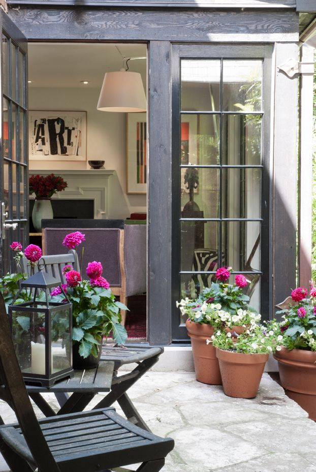 Outdoor living on the porch - I like the black french doors & Chairs with the pops of colors in the flowers