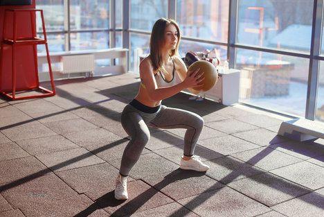 Existuje spousta variant, jak dělat dřep. Pokud chcete posílit i horní část těla, cvičte napříkad s medicinbalem; vladee, Shutterstock.com