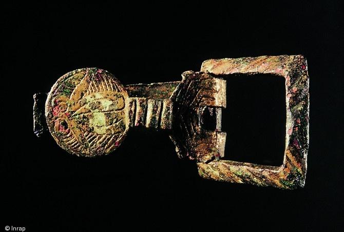 Boucle de ceinture en bronze, Xe-XIe s., Pineuilh (Gironde), 2002-2003.  La richesse du mobilier exhumé sur le site traduit l'aisance des propriétaires des lieux.  © Frédéric Prodéo, Inrap