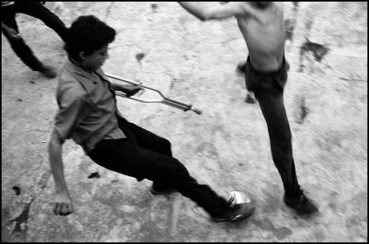 Larry Towell, EL SALVADOR. Perquin, Morazan, 1992. Fourteen-year-old guerilla playing soccer with friends and other youth his age. Children are drawn into war, wounded or killed.