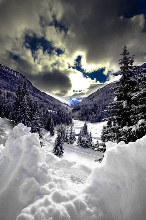 Winter Magnificence - white clouds float past a brilliant sun that shines down over the soft snow in the mountains.