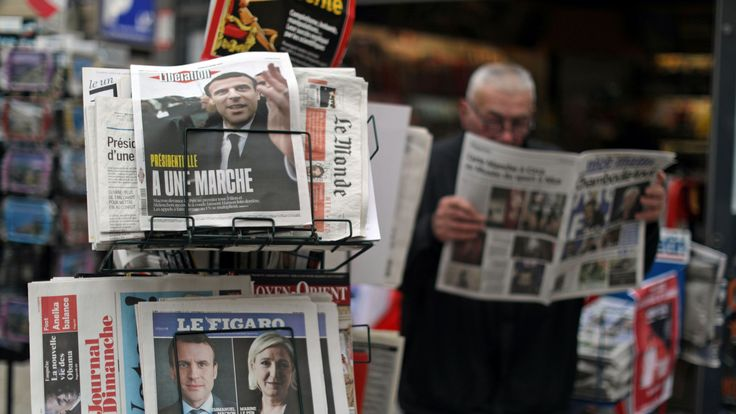 A man reads the local newspaper near a rack which displays copies of French daily newspapers with front pages about the results in France's Presidential election in Nice, France, April 24, 2017. REUTERS/Eric Gaillard