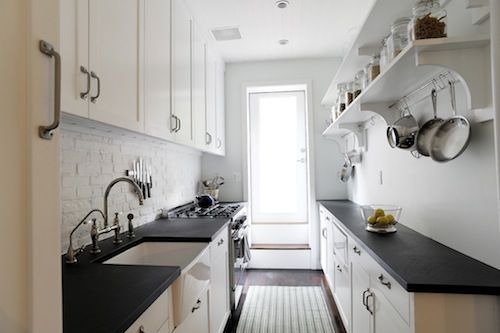 Great galley kitchen. looks like slate or soapstone counters.  Love the hanging pots and open high shelving