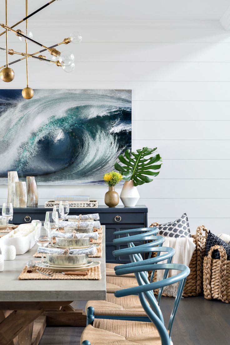 modern beach house dining room with shiplap and wishbone chairs, baskets and blue sideboard