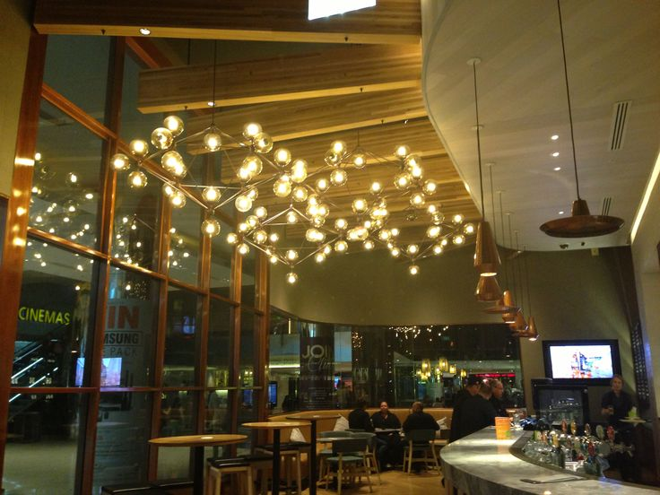 different source and shape in each corner. small glass bubbles light with aluminum. different shape of wood lighting on top of bar bench