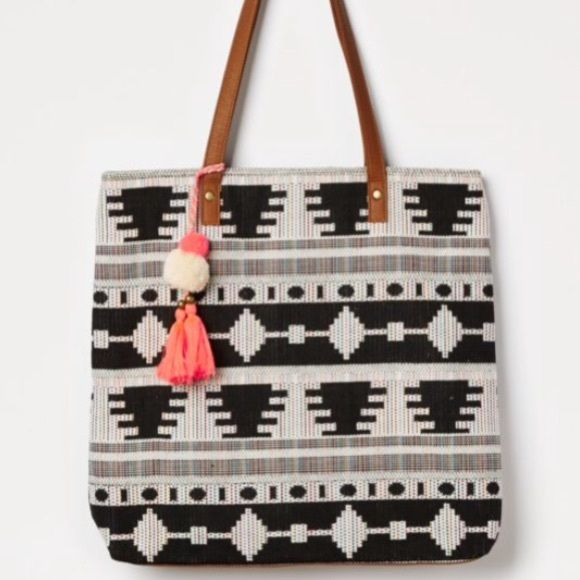 T-SHIRT & JEANS Black Aztec TOTE W TASSEL Keychain BRAND NEW w/ TAGS!! A festival-ready tote bag that's perfect for the music scene! It features a detailed Aztec-inspired woven pattern with colorful threads, plus a pop of neon in the form of the pom-pom tassel charm it comes with. Faux leather base and straps. * By T-Shirt & Jeans® * Height: 14.5 in. *              Base: 14.5 x 3 in. * Magnetic snap closure * Interior pockets  *              Zip compartment * Woven lining…