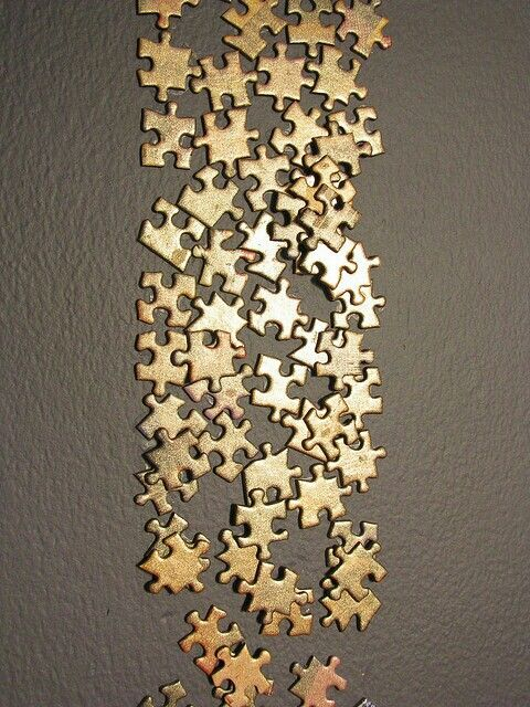 Paint your old puzzle pieces with gold or silver and stick them on the wall!!Looks expensive