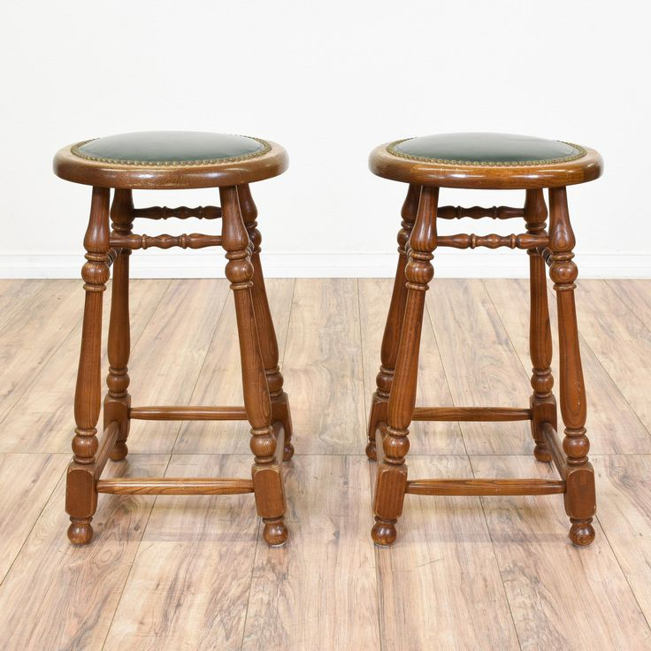 This pair of barstools are featured in a solid wood with a glossy dark maple finish. These stools are in great condition with carved spindle details, brass nailhead trim and a dark green vinyl upholstered seat cushion. Perfect for a game table! #traditional #chairs #barstool #sandiegovintage #vintagefurniture