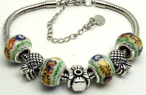 SC114 Handmade silver charm bracelet, on snake chain, with flower and pineapple charms and porcelain European beads. Normally retails for around $25 each - my selling price (including postage within Australia) is $15.00 each... Please feel free to contact me if your require price for postage overseas…