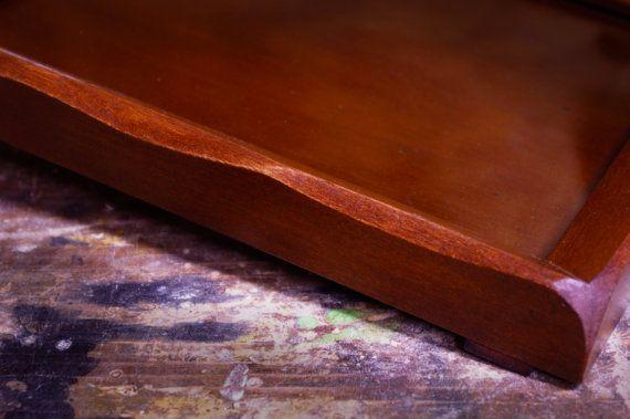 Vassoio in legno di noce tanganica. Completamente fatto a mano secondo l'esperienza e la tradizione artigianale calabrese. Finitura trasparente lucida. Due manici laterali e piano in vetro smontabile per poterlo personalizzare. Dalle geometrie semplici e naturali, con bordi irregolari, questo prodotto è ispirato alle forme uniche e spontanee della natura. L'irregolarità delle forme e la caratteristica lavorazione artigianale, rendono ogni esemplare di questo prodotto assolutamente unico…