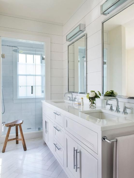 White shiplap bathroom is fitted with two polished nickel framed vanity mirrors mounted beneath nickel and frosted glass box lights over a white washstand accented with polished nickel pulls, a polished nickel towel bar, and rectangular sinks paired with polished nickel faucets.