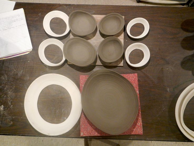 I threw the bottomless rings on the potter's wheel, ovalized them, and bisque-fired them. They can be used repeatedly now. Then I threw flat plates (8 oz, 11 oz, & 3 lbs) on the wheel, stretched them oval a little on canvas, and slumped them into the oval bisqued rings. Voila! Nice freeform little bowls and serving plate.