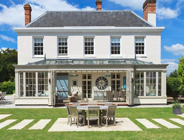 A detatched white Georgian house with the conservatory added to the back with a lawn and patio furniture.Combined with modern innovations, such as bi-fold doors which open the front wide, the period-style columns and 12-pane windows make sure this conservatory dining and relaxing space complements the Georgian house. Bespoke conservatories from Vale Garden Houses cost from £35,000. 01476 564433; Vale Garden Houses