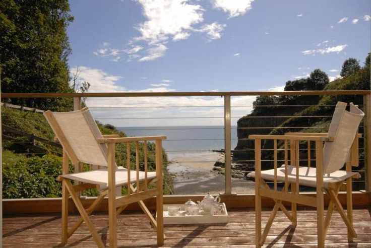 Enjoy tea on the balcony overlooking the sheltered little cove of Waterwynch Beach