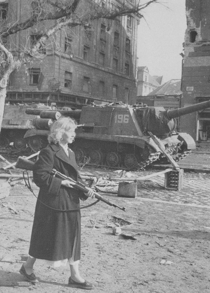 The Hungarian Revolution of 1956: a young Hungarian girl emerges from a building housing resistance fighters carrying a rifle.