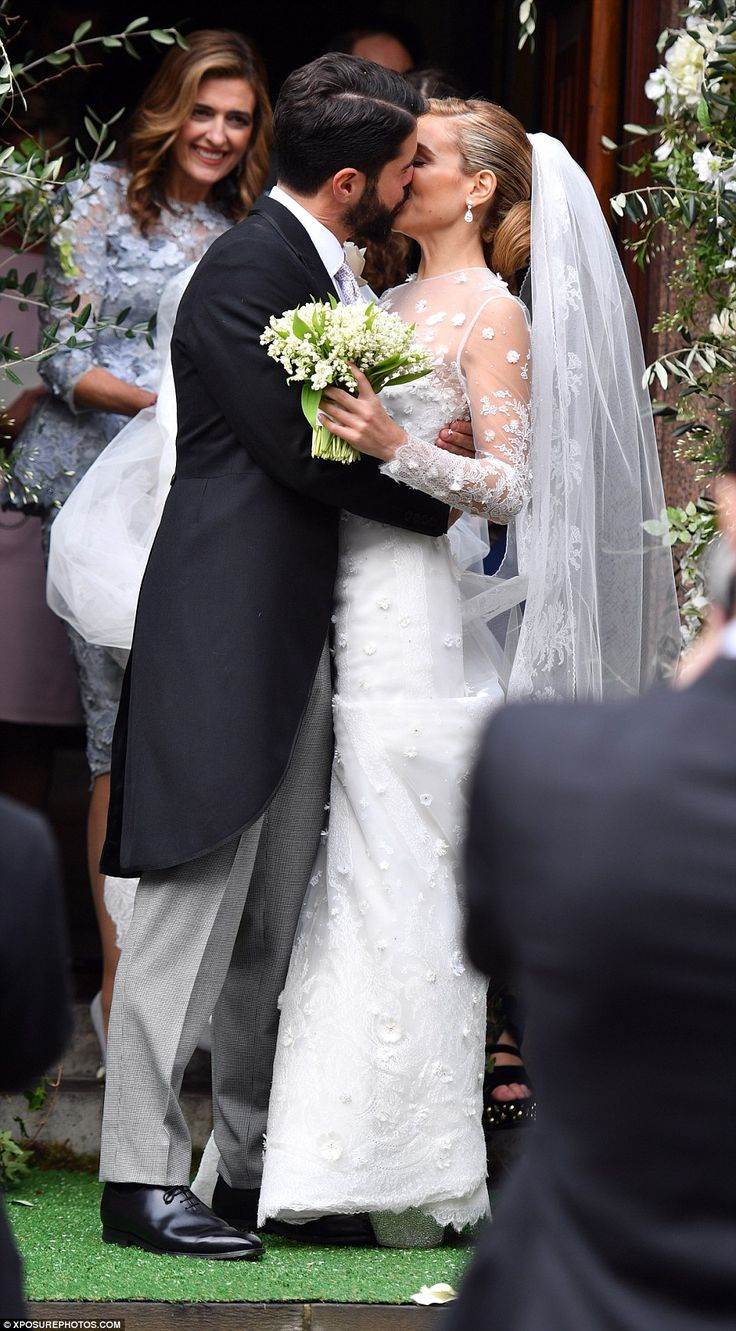 They newlyweds steal a kiss outside the church, much to the delight of onlookers