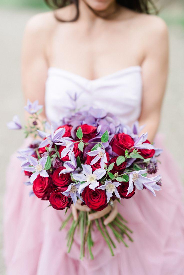 En färgglad, romantisk brudbukett i rött och lila. Innehåller rosor med klematis och hortensia.