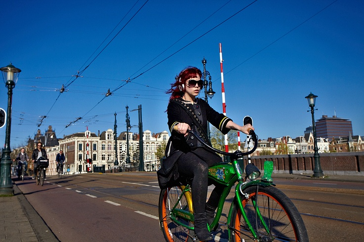 Girl on bike passing by at the Nieuwe Amstelbrug in Amsterdam..Click on the picture above to see more Amsterdam bikers!