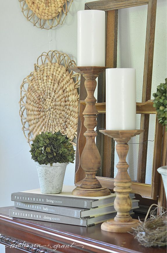 Rustic wood candlesticks and boxwood decorating the living room.