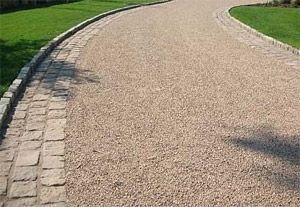 Tar and chip driveway. This has an upscale look with the cobblestone edging. The raised curbing will work great. And although I like the look of the triple border, I would imagine this will take some upkeep.