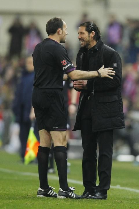 Atletico's coach Diego Simeone, right, talks to the referee during a Spanish La Liga soccer match between Atletico de Madrid and FC Barc...