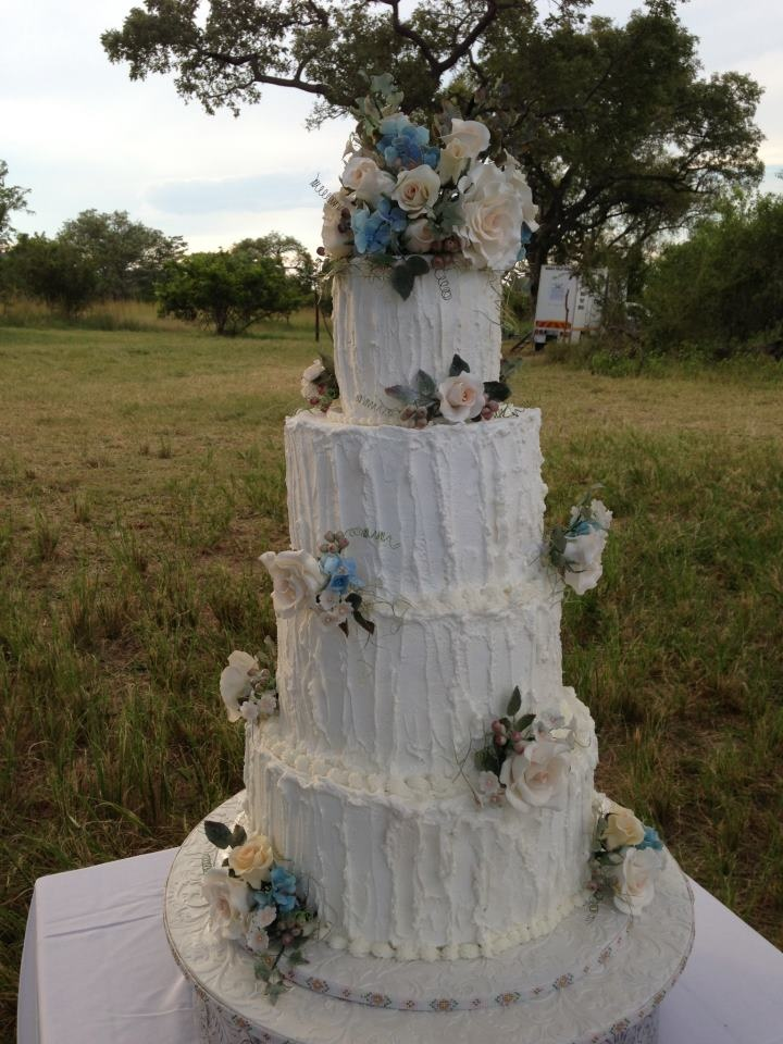 4 tier white cake with sugar flowers, roses, hydrangias and fillers.