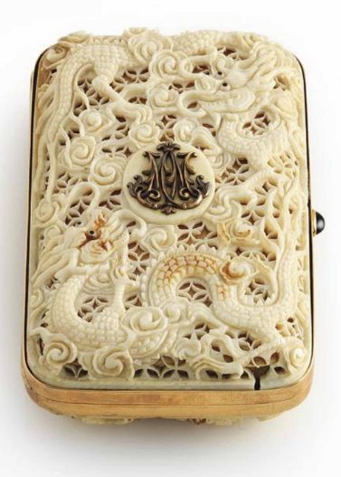 A RUSSIAN JEWELLED GOLD-MOUNTED AND IVORY CIGARETTE-CASE STRUCK WITH THE STANDARD RUSSIAN MARK FOR 14 CARAT GOLD rectangular box with rounded corners, the cover and base overlaid with ivory cagework intricately pierced and chased with scrolls and sea-serpents, the cover set with the raised gold cypher for Nicolas II (1868-1918), Tsar of Russia 1894-1917, polished gold sides with sapphire cabochon push-piece.