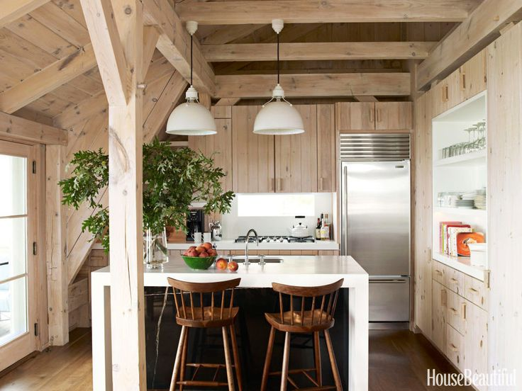 """""""The most vivid example of combining humble materials with precious ones is in the kitchen,"""" David Netto says of the kitchen in a Southampton, New York, beach cottage. He tucked Nero Marquina marble under a white Corian island, """"concealing it for maximum impact and surprise."""" The slot window over the stove is also a pleasant surprise. Will Meyer """"designed it in a burst of inspiration."""""""