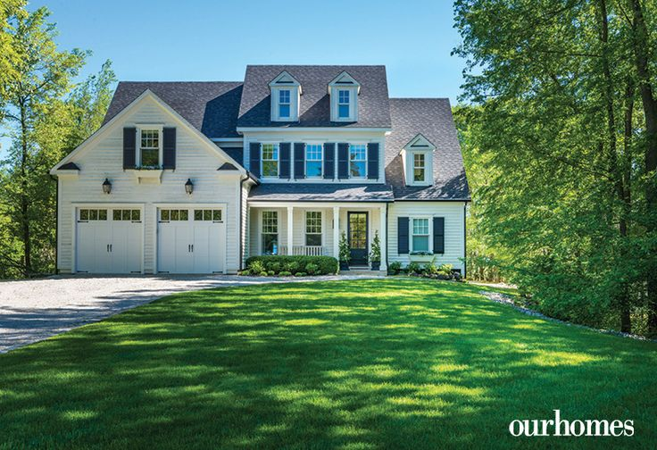 "With its modified New England saltbox architecture, the inviting front facade of the home has proportioned windows and dormers. Window boxes and urns are by Kettlewells.     See more of this home in ""Cape Cod Style Home on the Shores of Georgian Bay"" from OUR HOMES Southern Georgian Bay, Summer 2017 http://www.ourhomes.ca/articles/build/article/cape-cod-style-home-on-the-shores-of-georgian-bay"