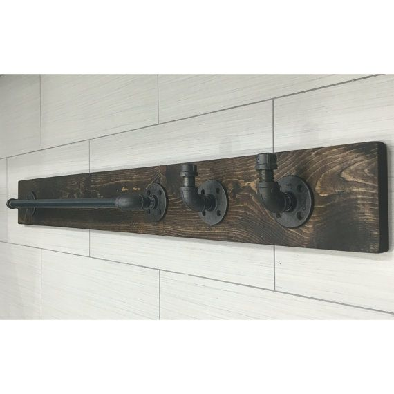 Industrial, rustic towel holder with two hooks.  ALL LIGHT FIXTURES AND ACCESSORIES ON WOOD CAN BE DONE IN BOTH STAIN COLORS ... JUST LET US KNOW.   DESCRIPTION: Add some industrial/rustic style to your bathroom, garage workshop or office. This item was created to add a touch of a class to your home. It will give you a space for a towel and 2 hooks for your extra towel or a cozy robe. The wood is custom hand distressed. No two pieces are alike. Its made out of wood and pipes. Both were clean…
