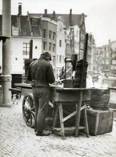 'Mosselman' achter kraam / stal met mosselen op het Singel (bij de Haarlemmerstraat) in Amsterdam.