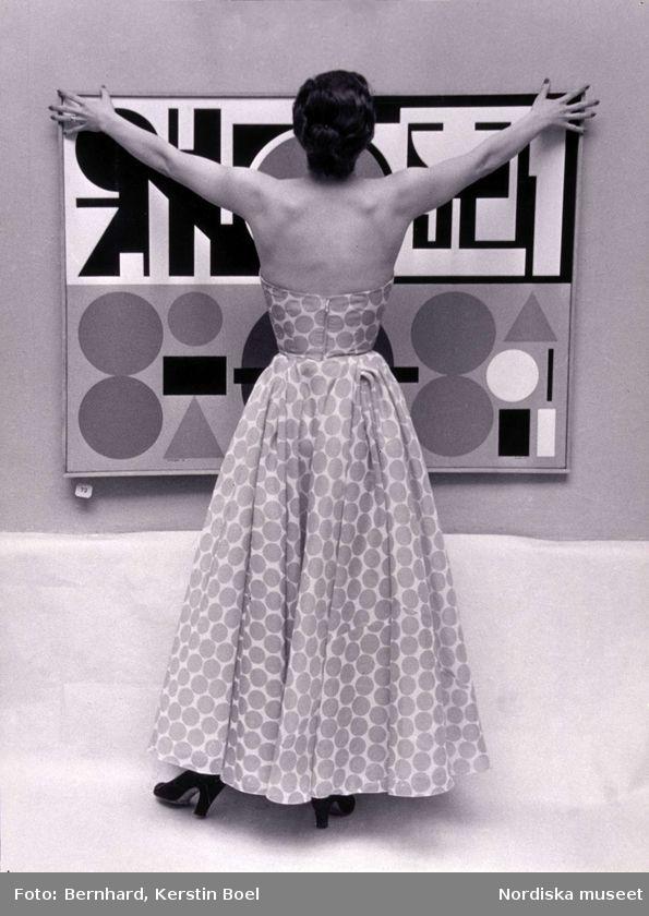 Modell i prickig långklänning står framför konstverk. Modereportage för Idun. Liljevalchs. 1952