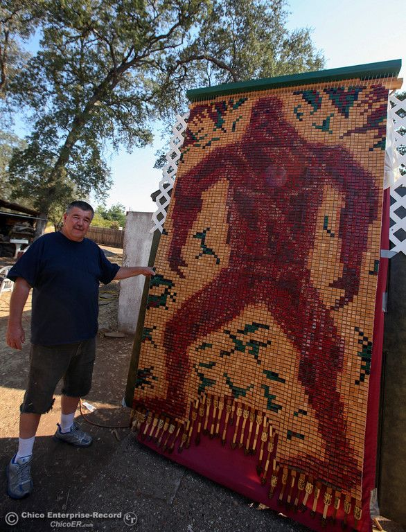 "Guy Gannett stands next to an extremely large beaded panel of his rendition of Bigfoot he is creating for the Salmon Festival. He's been consumed with this project, his aunt thinks he's ""nuts"" and sometimes he bores people because that's all he wants to talk about. Guy watched  his grandmother loom beads as a child then learned himself.  Oroville, California September 9, 2014. (Emily Bertolino - Mercury Register)"