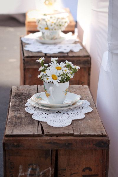 teacups of daisies on wooden crates