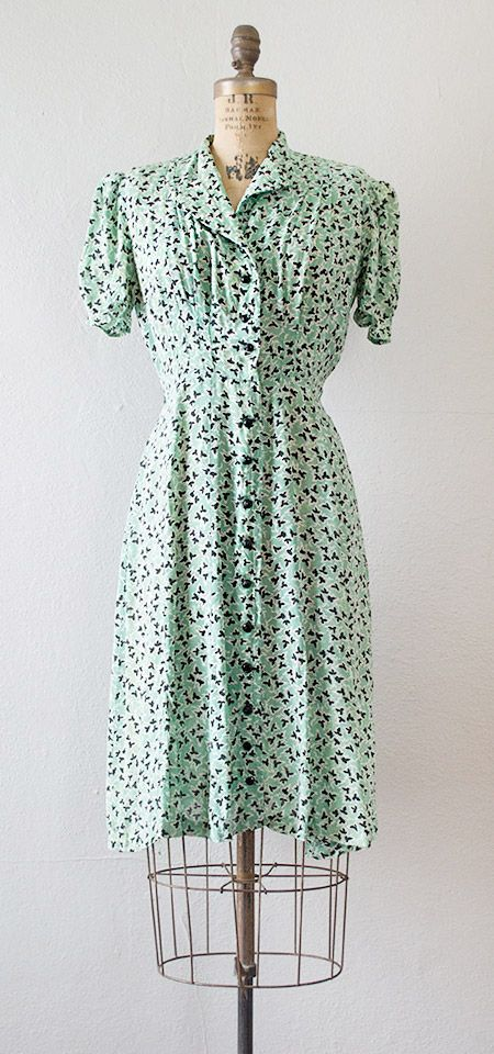 1930s mint green and black print day dress with short puffed sleeves, slightly padded shoulders, and released tucks from the top that meet into pleats from the waist creating a very tailored flattering fit. Black multifaceted buttons march down the front. Via Adored Vintage.