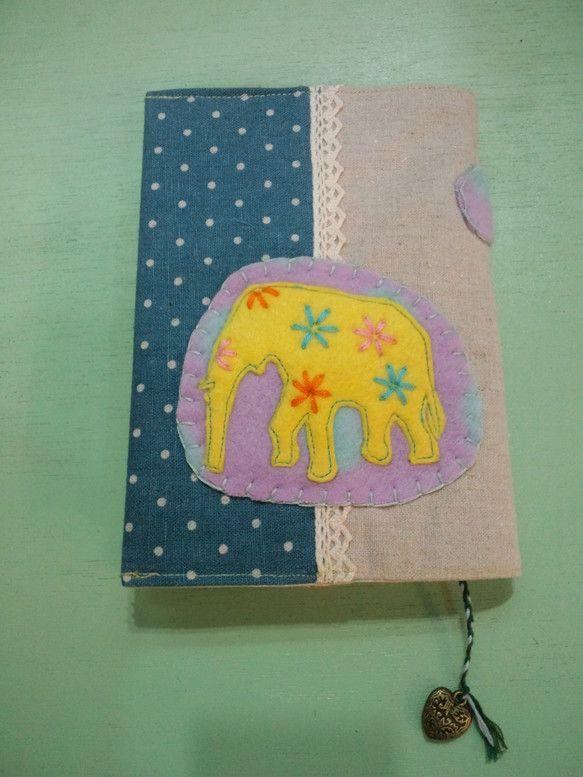 実店舗でsold outフェルトでゾウのアップリケをしたブックカバーを作りました。文庫サイズです。栞は刺繍糸を三つ編みしています。栞の先にハートのチャームをつ...|ハンドメイド、手作り、手仕事品の通販・販売・購入ならCreema。