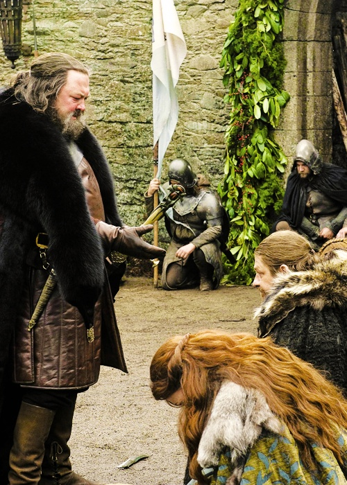 King Robert Baratheon comes to Winterfell; Ned Stark, Catelyn Stark, kneeling