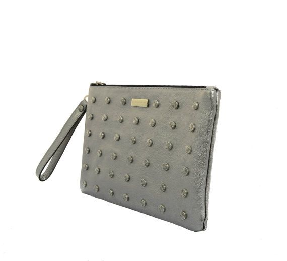 This silver leather clutch bag from MONAO is embellished with studs for an edgy look. Crafted in high quality italian leather will add a glamourous finish to all your evening looks. Perfect for pairing with a little black dress and leather jacket  Details:  Material: italian leather Colour: silver Top zipped fastening Wrist strap Fully lined Slip on inside pocket Stud embellishment on the front Metal logo plaque  Dimensions: Height: 17cm (6,5) Width: 27cm (10,5)