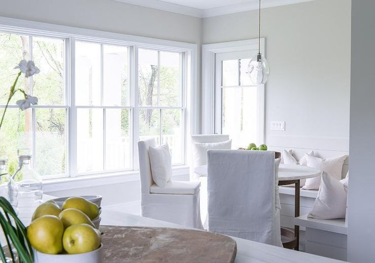 Natural light shines in through a wall of windows and a glass paneled patio door framed by pale gray walls in this stunning light and airy breakfast room featuring three white slipcovered dining chairs placed around a round marble top dining table also seating an l shaped shiplap dining bench topped with white pillows and lit by the glass pendant hung over the dining table.