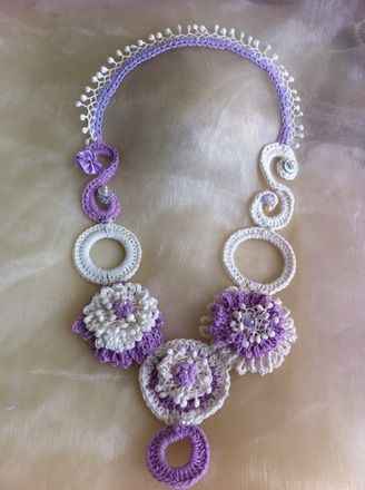 Joli collier pleines fleurs en crochet (coton) dans les tons lilas et écru orné de perles de verre, perles de nacre et boutons nacrés. Ce collier mi-long se porte idéalement su - 14299215