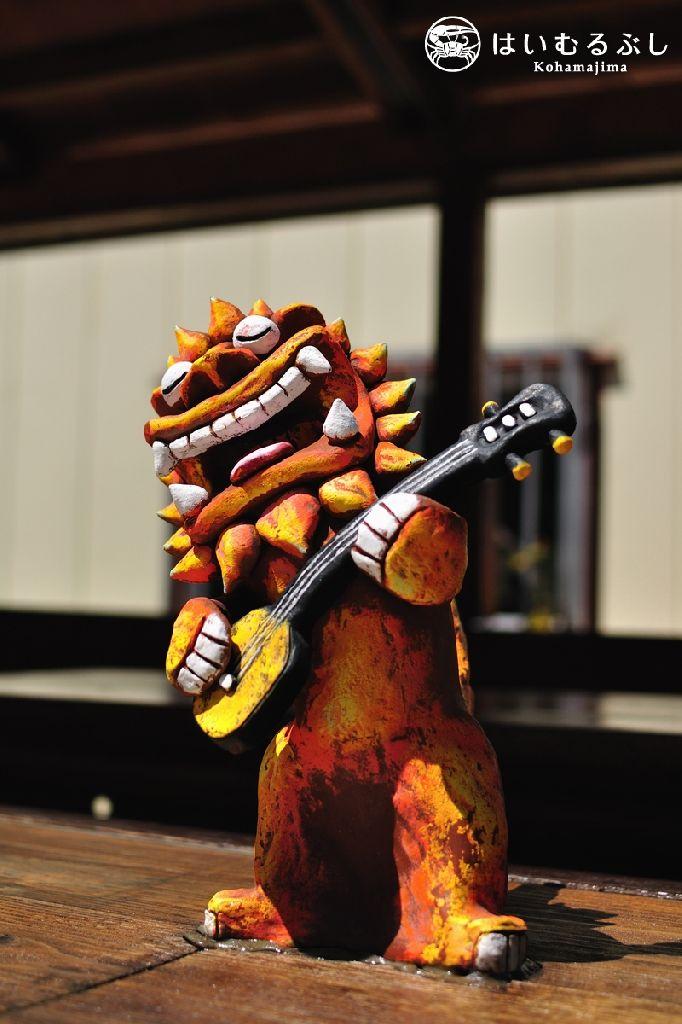 Shisa playing sanshin Taketomi Okinawa 三線を弾きながら、気持ち良さそうに唄っているシーサーの像。 視ているだけで幸せな気分にさせてくれますね… 竹富島・竹富観光の待合所にて撮影。竹澤雅文