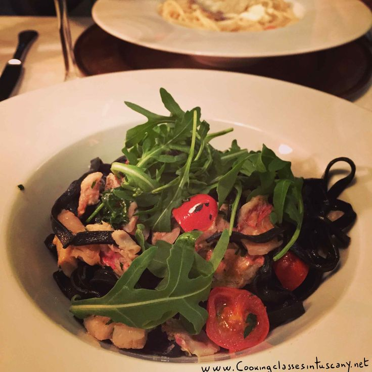 Squid Ink Tagliatelle (fresh pasta) with red mullet, rucola and piccadilly tomatoes. Directly at your home with our cooking classes and dinners in Tuscany.