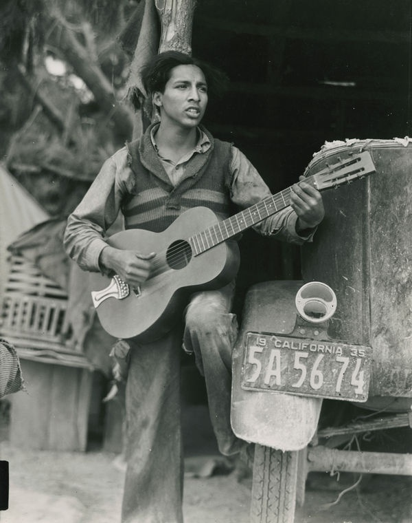 A young Mexican farm worker plays guitar and sings in a Coachella Valley labor camp. 1935. Dorothea Lange, photographer.