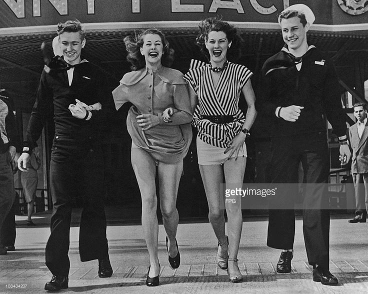 Two women, with their skirts blown up by the wind, out with two sailors circa 1940.