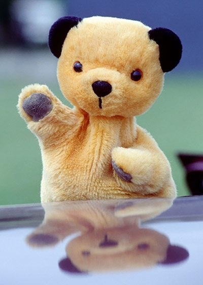 """Sooty acquired his name when his ears were darkened with soot so they would stand out on black-and-white television. He is known for having a magic wand and a water pistol, for being mute but casting a spell when he says: """"Izzy wizzy let's get busy"""", and for playing the xylophone. A staple of children's TV in the 50s, his domestic arrangements were weird: he shared a house with Sweep the Dog."""