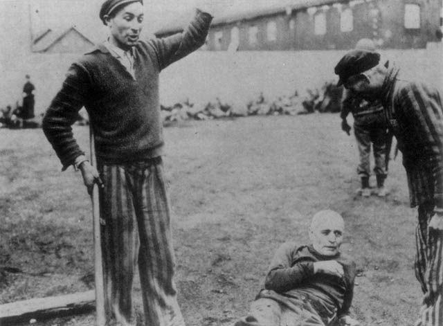Former inmates of Dachau Concentration Camp moments away from executing an SS guard with a shovel on the day of the camp's liberation.    Dachau, Germany - April 29, 1945