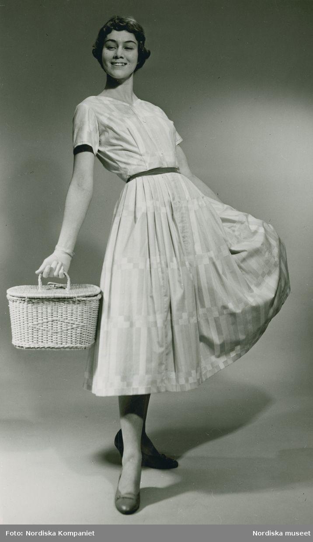 Brud och Hem, 1957. Modell i mönstrad klänning, handskar och korg i handen. Foto: Erik Holmén för Nordiska Kompaniet.