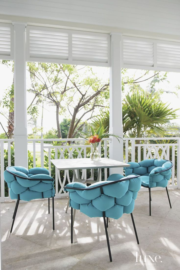 The lanai affords tropical views and comfortable seating through whimsical Ligne Roset chairs with bold turquoise cushions. The chairs surround a branch dining table by Janus Et Cie.